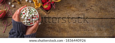 Hot chocolate with marshmallows, warm chocolate drink for Christmas morning breakfast, on wooden background with Christmas decorations, cozy winter pic. Hot chocolate cup in girls hands