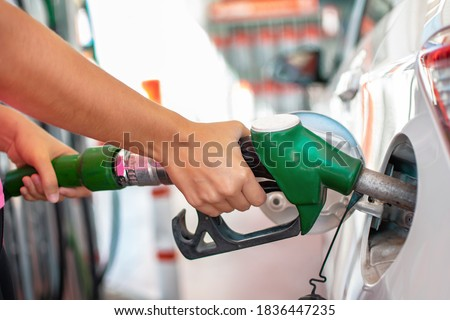 Filling up the car with petrol. Woman's hands pouring gasoline or gas into her car tank at fuel station Royalty-Free Stock Photo #1836447235