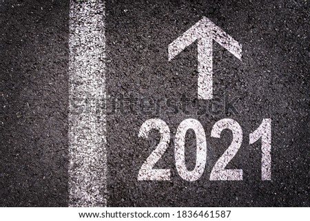 2021 and a direction arrow written on an asphalt road background, urban new year greeting card Royalty-Free Stock Photo #1836461587