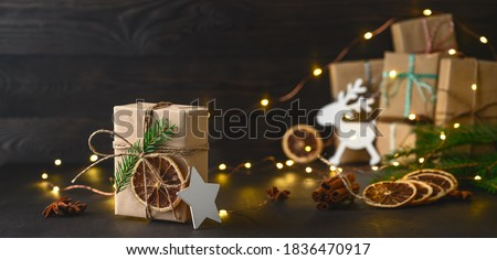 Christmas zero waste concept. Eco friendly packaging gifts in kraft paper on a dark wooden table. DIY gifts, eco decor. Copy space, banner. #1836470917