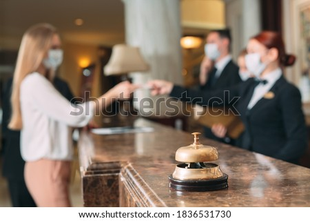 Check in hotel. receptionist at counter in hotel wearing medical masks as precaution against virus. Young woman on a business trip doing check-in at the hotel Royalty-Free Stock Photo #1836531730