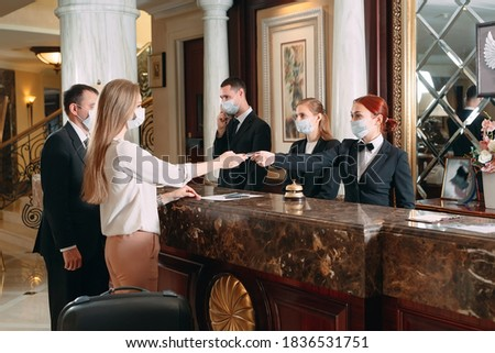 Check in hotel. receptionist at counter in hotel wearing medical masks as precaution against virus. Young woman on a business trip doing check-in at the hotel #1836531751