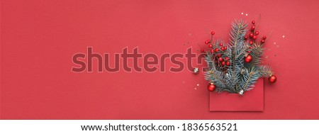 Banner with concept of Christmas tree in red envelope on red background. New Year greeting card with copy space.