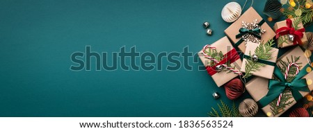 Banner with many gift boxes tied velvet ribbons and paper decorations on turquoise background. Christmas background.