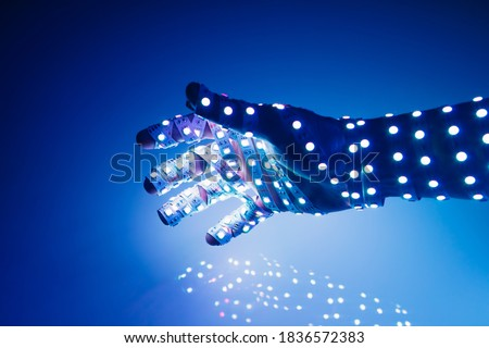 human hand covered with blue led lights, illuminated background Royalty-Free Stock Photo #1836572383