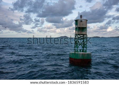 Marine buoy at sunset in the rippling Caribbean Sea under a cloudy sky off the coast of St. Croix in the USVI Royalty-Free Stock Photo #1836591583