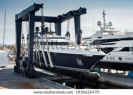 Super Yacht hauled out in shipyard, being lifted by industrial crane for refit or maintenance yard period  Royalty-Free Stock Photo #1836626470