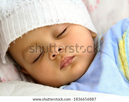 baby sleeping wrapped up in blanket after having a good sleep in bed stock photo