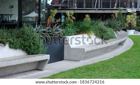 Curved pre cast concrete bench seating and a garden behind the seating. Modern terrazzo concrete curved bench seats in a public space with buildings in the background. Barangaroo Royalty-Free Stock Photo #1836724216