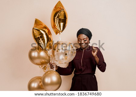 Muslim new year party with golden balloons for black woman. African attractive girl celebration of the end of year. Happy emotion Royalty-Free Stock Photo #1836749680