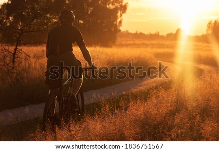 Cyclist riding a trail in a field on a gravel bike on a dramatic sunset background. Sport and active lifestyle concept. Royalty-Free Stock Photo #1836751567