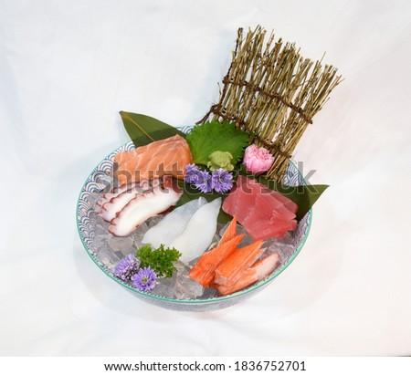 Japanese Sashimi Set with raw sliced salmon, tuna, squid, octopus and crab sticks topped on ice in a big bowl, isolated in white background. Simply use for japanese restaurant as picture menu