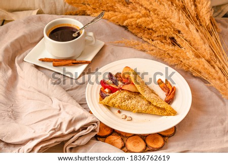 gluten-free keto crepes with peach and almonds and sweet berries. a cup of coffee with cinnamon. selective focus. autumn healthy breakfast or dessert concept. #1836762619
