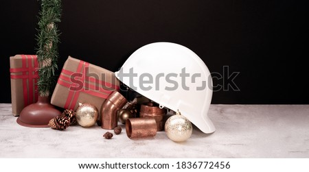 Construction hard hat and plumbing items with Christmas and New Year decoration over holiday Horizontal background.