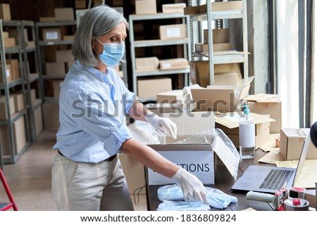 Mature female volunteer warehouse worker wearing face mask working in shipping delivery charitable stock organization packing medical donations box. Covid 19 coronavirus donating and volunteering. Royalty-Free Stock Photo #1836809824