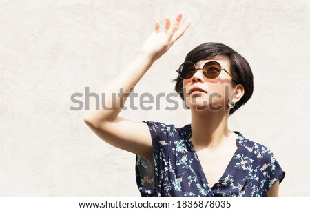 Beautiful & Stylish Asian woman wearing 100% UV light eyes protection sunglasses, stand and raise her hand to block out bright glare and sunlight to avoid ultraviolet rays. UV exposure, Aging, Optical Royalty-Free Stock Photo #1836878035