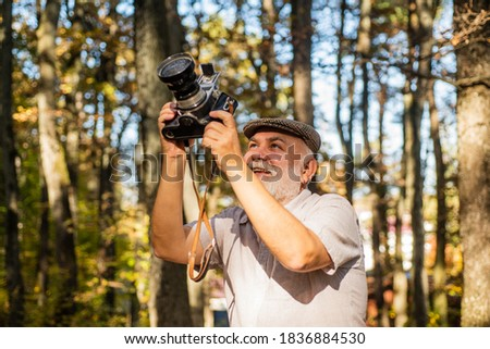 Best camera for professional. Old photographer on autumn day. Pensioner hold vintage camera in forest. Elderly man with photo camera. Using analog camera for shooting. Nature photo shoot session.