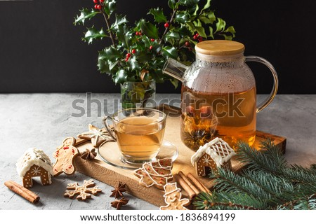 Glass teapot with blossoming tea and tea cup on grey table with Christmas gingerbread cookies. Christmas holiday tea ceremony. #1836894199