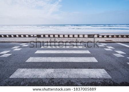 Zebra crosswalk on ocean ocean promenade. Royalty-Free Stock Photo #1837005889