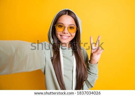 Photo of beautiful brunette hair kid show arm finger v-sign on selfie hoodie isolated on yellow color background