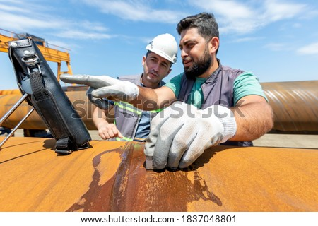 Non-destructive testing technicians are checking welds of pipe with ultrasonic testing (UT) method. Ultrasonic testing is often performed on steel and other metals and alloys. Royalty-Free Stock Photo #1837048801