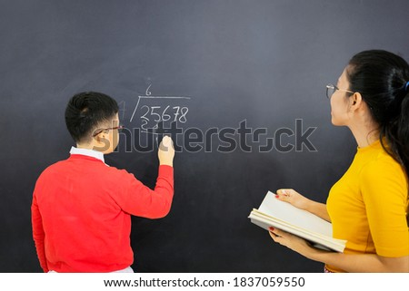 Picture of male student learns math with his female teacher while writing on chalkboard and standing in the classroom