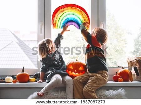 Preschool children on background of painting rainbow on window.  Family preparing for celebrating Halloween during quarantine Pandemic Coronavirus Covid-19 at home. Kids leisure activities indoors.