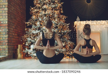 Beautiful woman and a girl go in for sports at Christmas near a decorated Christmas tree, sports and holiday. High quality photo.