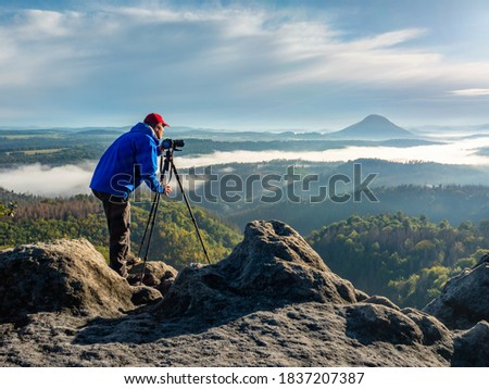 Working photographer in mountains.  Nature photographer traveler taking photo of beautiful morning landscape from top of the mountain