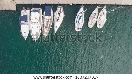 Aerial top down picture of yachts anchored in port.