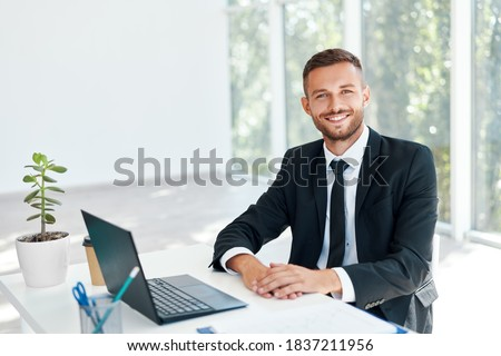 Stylish smiling businessman in elegant suit sitting at his desk in a bright modern office. business success concept Royalty-Free Stock Photo #1837211956