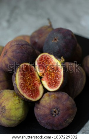 Fresh figs. A few figs on a black cutting board. Whole figs and one fig sliced. The flesh of the fruit is pink and has a mild, sweet taste. The scientific name for the fig is Ficus carica.  #1837229392