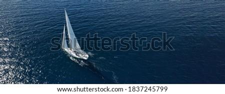 Aerial drone ultra wide photo of beautiful sailboat cruising deep blue open ocean Mediterranean sea