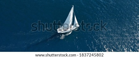 Aerial drone ultra wide photo of beautiful sailboat cruising deep blue open ocean Mediterranean sea