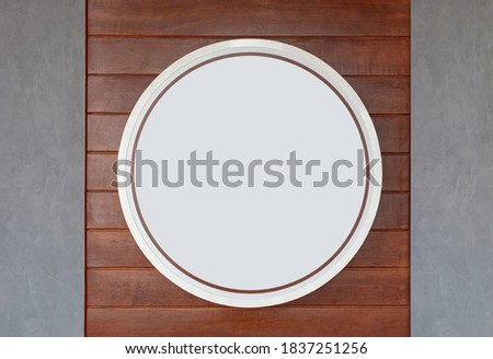 Empty white circular Lightbox sign hanging on a wooden wall and concrete wall. Copy space for text. Can used for advertising business concepts.