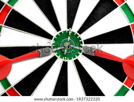 Close-up of a dart board with an imprinted flag of State of Washington in the center. The concept of achieving goals.
