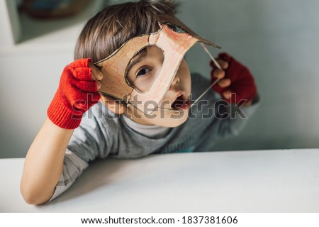 Cute kid in disguise with DIY  cardboard superhero mask at home. Boy with creative Halloween costume or festive apparel for children theater. Playful spirit concept. Home celebration with family. Royalty-Free Stock Photo #1837381606