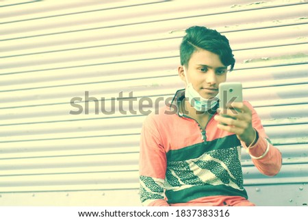 An indian young student using a smartphone. Copyspace stock image.