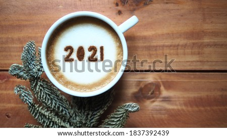 Welcome 2021 theme coffee cup with number 2021 on frothy surface flat lay on wooden table background with dried pine branches. Happy new year 2021, Holidays food art concept. (close up, top view) #1837392439