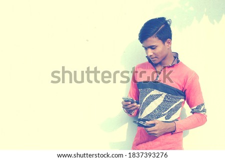 An indian young student using a smartphone. Concrete wall background Copyspace stock image.
