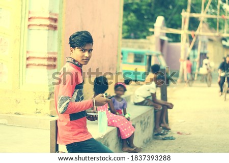 An indian young student using a smartphone in a galli/para more. Copyspace stock image. Childrens playing outside in the park.