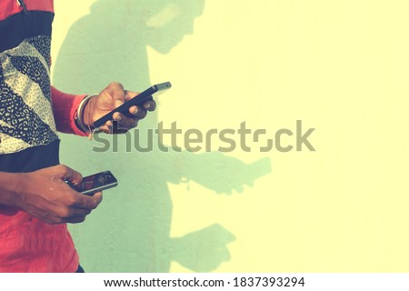 An indian young student with his shadow in the wall using a smartphone. Copyspace stock image.