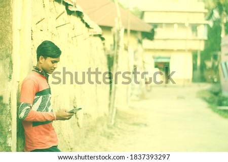 An indian young student using a smartphone.Clay house wall with road. Copyspace stock image. Blurry background.