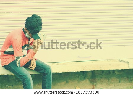 An indian bored/sad/depressed/tensed young student sitting and holding mobiles.Copyspace stock image.