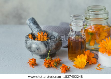Calendula products. Bottle of cosmetic, aromatic or essential oil and fresh and dry calendula flowers on white background. Aromatherapy, spa and wellness concept