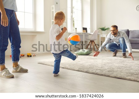 Happy young family staying at home, having fun together and engaging their small kid in sport games. Dad with little son playing soccer with inflatable ball in cozy living-room Royalty-Free Stock Photo #1837424026