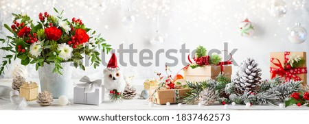 Christmas or New Year concept with flower arrangement, gift boxes and Christmas decorations on table. Festive still life. #1837462573