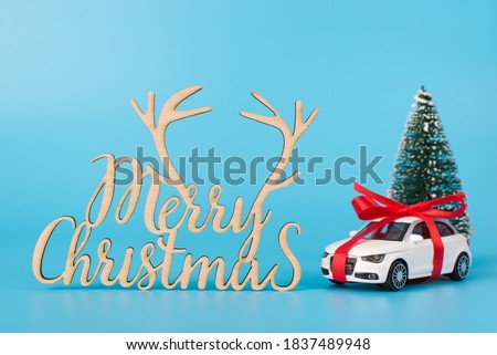 Merry Christmas postcard concept. Photo picture of present car with ribbon bow fir tree and invitation congratulation text isolated blue background