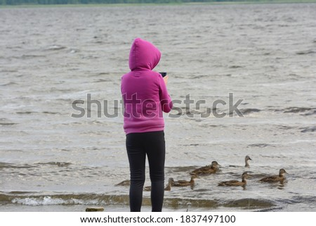 A girl in a hood stands with her back and takes pictures on her smartphone of ducklings and a duck floating by on the river