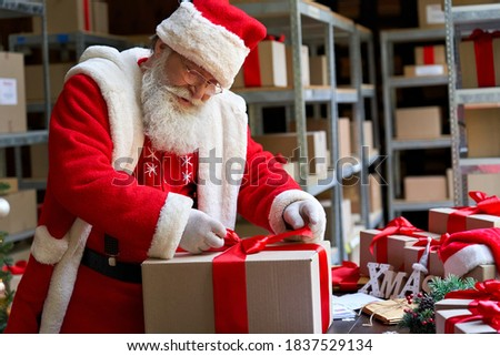 Happy old bearded Santa Claus, Saint Nicholas packing present box wrapping gift with red ribbon preparing post shipping delivery parcel on table in workshop. Merry Christmas shipping delivery concept. #1837529134